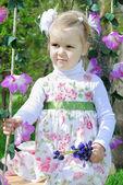 Beautiful little girl on a swing in a beautiful dress — Stock Photo