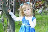 Dziewczynka na zielonej trawie wiosną kwitnące drzewo — Zdjęcie stockowe