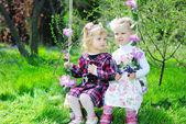 Two little girls girlfriend on a swing — Stock Photo