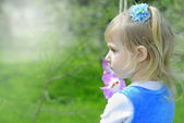 Little girl on green grass in the spring in a Blue Dress — Stock Photo