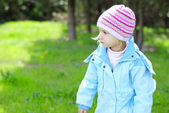 Little girl on green grass in the spring in the park for a walk — Stock Photo