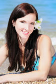Beautiful girl on the beach with a white flower in her hair — Stock Photo
