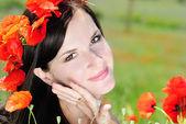 Bella ragazza con una ghirlanda di papaveri in un campo — Foto Stock