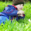 Stockfoto: Little boy on green grass