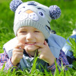 Little boy on a green meadow showing teeth — Foto de Stock