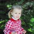 Stock Photo: Beautiful little girl on green meadow in beautiful red dress