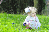 Little girl on a green meadow in a beautiful dress — Stock Photo