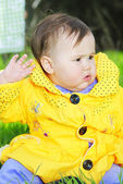 Little girl on a green meadow in a bright yellow jacket — Stock Photo