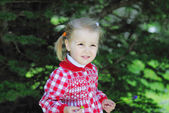 Beautiful little girl on a green meadow in a beautiful red dress — Stock Photo