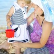 Little girl with her mother on the shore of the sea in the summe — ストック写真