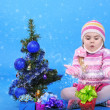The little girl with the Christmas tree and gifts — 图库照片