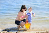 A little boy with his mother on the shore of the sea in the summ — Stock Photo