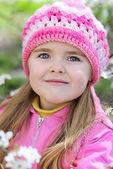 Beautiful little girl near a flowering tree — Stock Photo