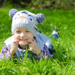 Little boy on a green meadow showing teeth — Stock Photo #33747529