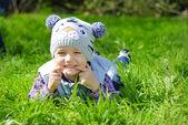 Little boy on a green meadow showing teeth — Stock Photo