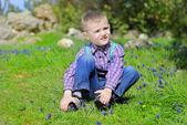 Kleiner junge auf einer grünen wiese — Stockfoto