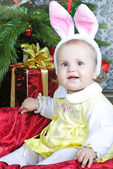 Small girl near new year's fir tree in suit of the bunny — Stock Photo