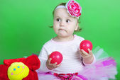 Small girl in rose suit on green background — Stock Photo