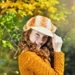 Young beautiful red-haired girl in the autumn park — Stock Photo