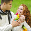 Young beautiful couple on green grass in autumn — Stok fotoğraf
