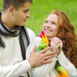 Young beautiful couple on green grass in autumn — Стоковая фотография
