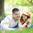 Young beautiful couple on green grass in autumn — Stock Photo