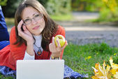 Young beautiful girl on a green meadow with a computer — Foto de Stock
