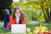 Young beautiful girl on a green meadow with a computer — Stock Photo