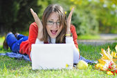 Young beautiful girl on a green meadow with a computer — Foto Stock