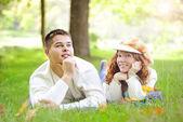 Junge schöne paar auf grünem gras im herbst — Stockfoto