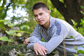 Bel giovane uomo in un parco verde — Foto Stock