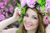 Beautiful girl in a flowered garden peach — Stock Photo