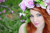 Beautiful girl in a flowered garden peach — Stock Photo