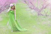Beautiful girl in the flowered garden peach — Foto de Stock