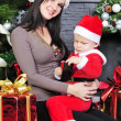 A little boy near the tree with her mother in a Santa suit — Stock Photo #37278367