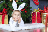 Small boy in suit of the bunny near new year's fir tree — Stock Photo