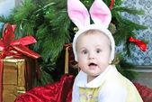 Klein meisje in de buurt van new year's fir tree in kostuum van het konijn — Stockfoto