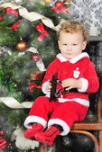 A little boy near a Christmas tree at Santa suit — Stock Photo