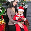 A little boy near the tree with her mother in a Santa suit — Stock Photo #37335541