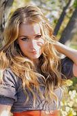 La chica joven y bella en madera de otoño en el sol — Foto de Stock