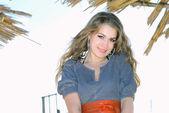 La hermosa joven sobre la arena de la costa cerca de una palmera en la una — Foto de Stock
