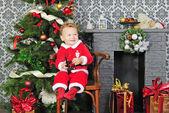 Een kleine jongen in de buurt van een kerstboom op santa pak — Stockfoto