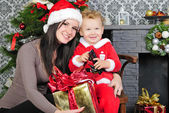 A little boy near the tree with her mother in a Santa suit — Stock Photo