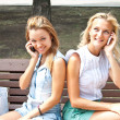 Two young women talking on the phone — Stock Photo