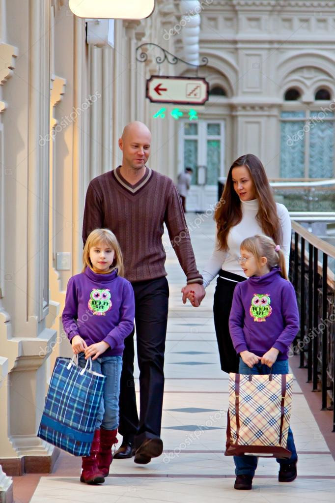 Father and mother with children walking in the mall and do your Christmas shopping — Stock Photo #16218067