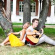 Man and woman with a guitar in the park — Stock Photo #17974509