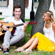 Man and woman with a guitar in the park — Stock Photo #17974525