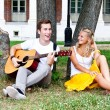Man and woman with a guitar in the park — Stock Photo #17974529