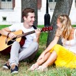 Man and woman with a guitar in the park — Stock Photo #17974541
