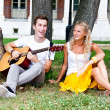 Man and woman with a guitar in the park — Stock Photo #17974549